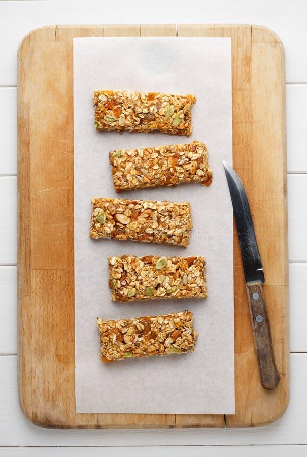 Barre di granola casalinghe di energia sul tagliere di legno con il coltello fotografia stock libera da diritti
