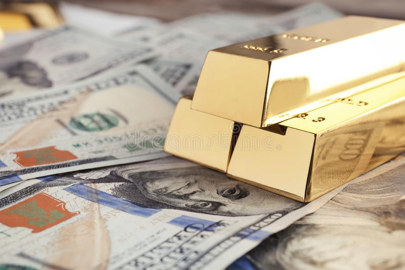 Barre di oro brillanti sul mucchio delle banconote in dollari fotografia stock libera da diritti