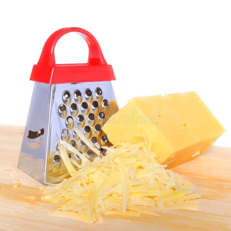 Barre el rallador del queso y el queso rallado en la tabla de cortar aislada fotografía de archivo