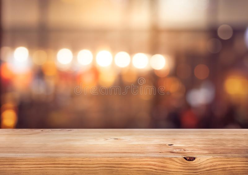Barre en bois de dessus de table avec le bokeh léger coloré de tache floue en café, fond de restaurant photo libre de droits