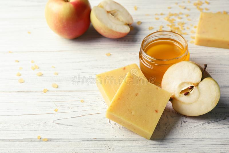 Barre fatte a mano, mela e barattolo del sapone di miele sulla tavola immagini stock libere da diritti