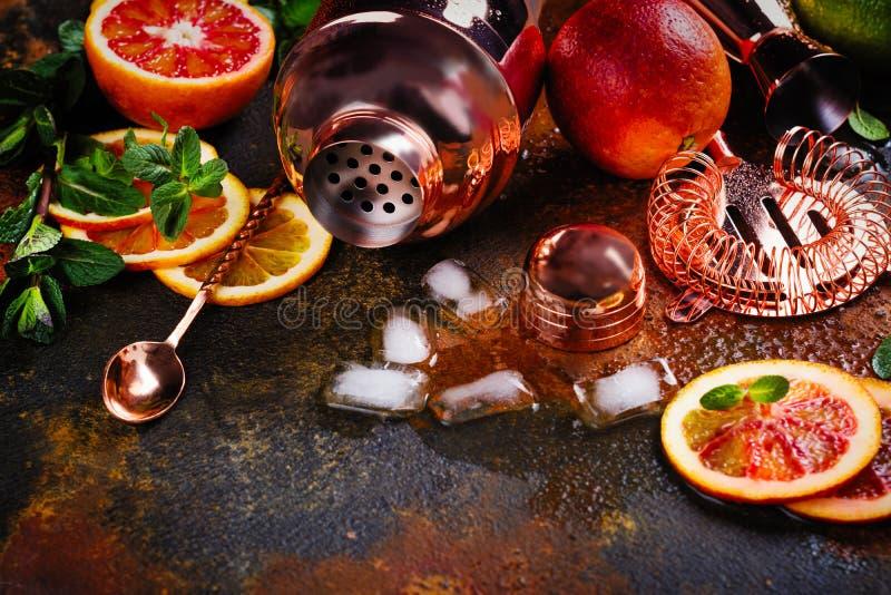Barre los accesorios, las herramientas de la bebida y los ingredientes del cóctel en la tabla de piedra oxidada estilo plano de l foto de archivo