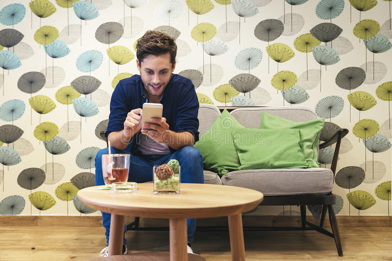 Barre a mensagem ocasional esperta da escrita do homem novo no smartphone foto de stock royalty free
