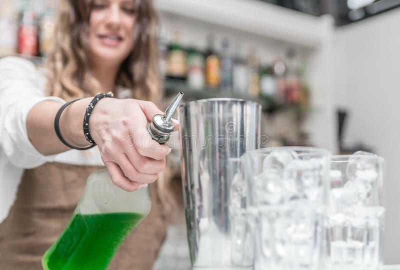 Barre a senhora que prepara cocktail e que derrama o álcool no glasse fotos de stock royalty free