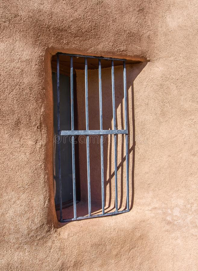 Barred Window at Ghost Ranch. Metal bars cover the window on an adobe wall at Ghost Ranch in northern New Mexico near Abiquiu stock photography