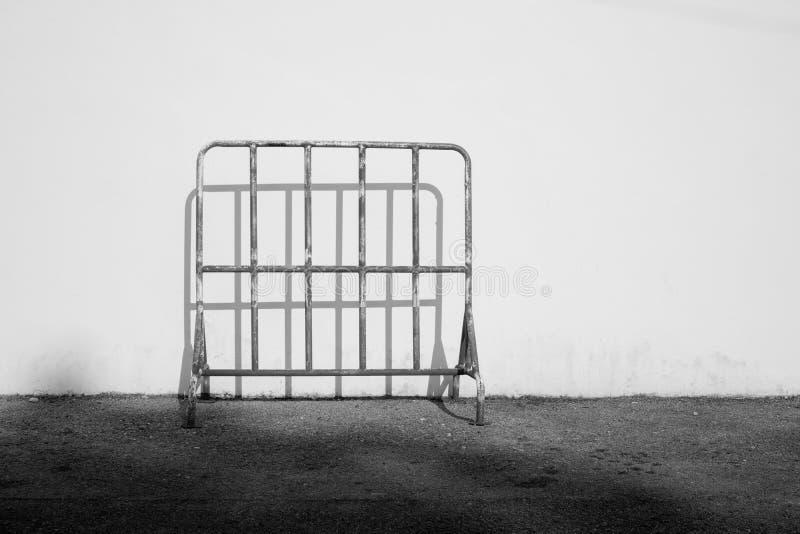 A barreira de aço velha do tráfego no asfalto moeu com fundo e sombra do cimento imagens de stock
