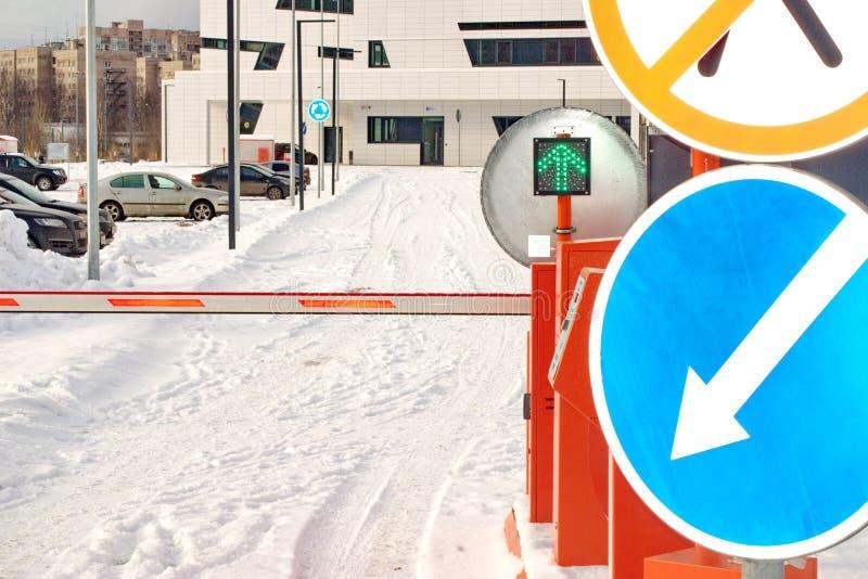 Barreira e sinais verdes na entrada ao parque de estacionamento pago fotografia de stock