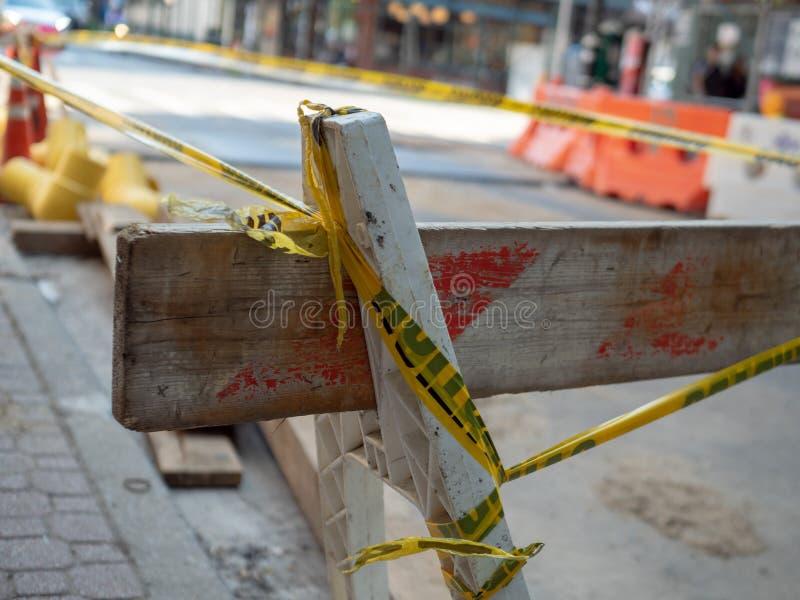 Barreiras de madeira da construção que sentam-se na esquina da rua envolvida na fita amarela do cuidado fotografia de stock royalty free