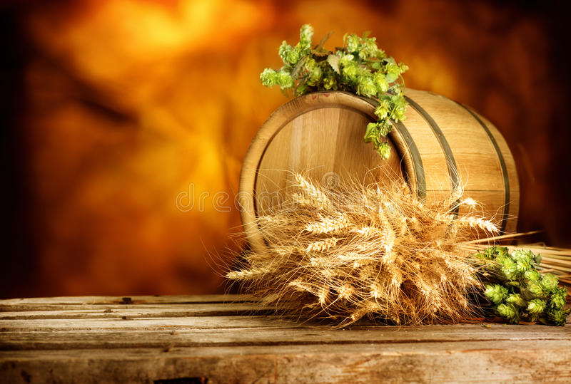 Barrel of beer with hop cones and ears wheat on vintage wooden table royalty free stock photo
