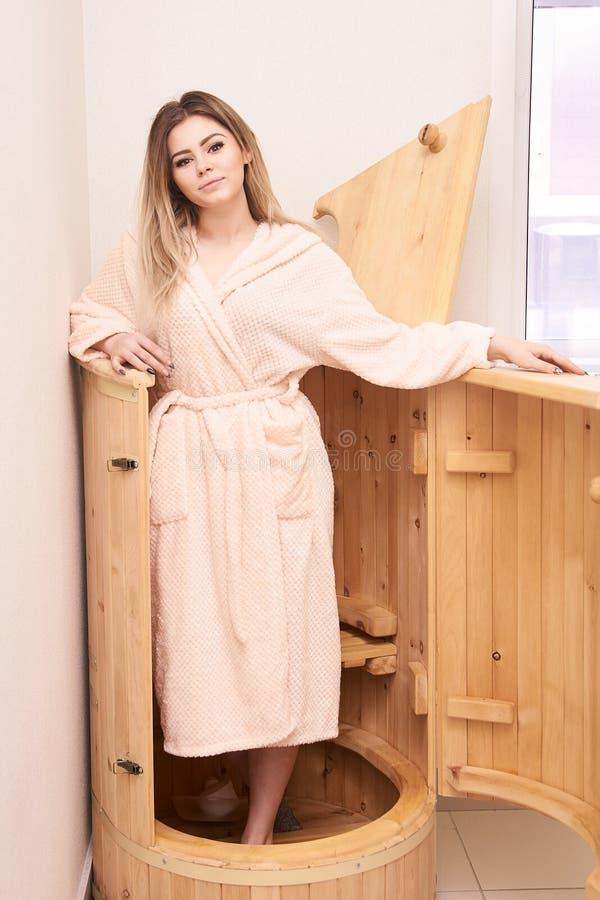 Barrel cedar. Wellness spa sauna. Aromatherapy treatment. Young beauty woman. Girl face stock photos