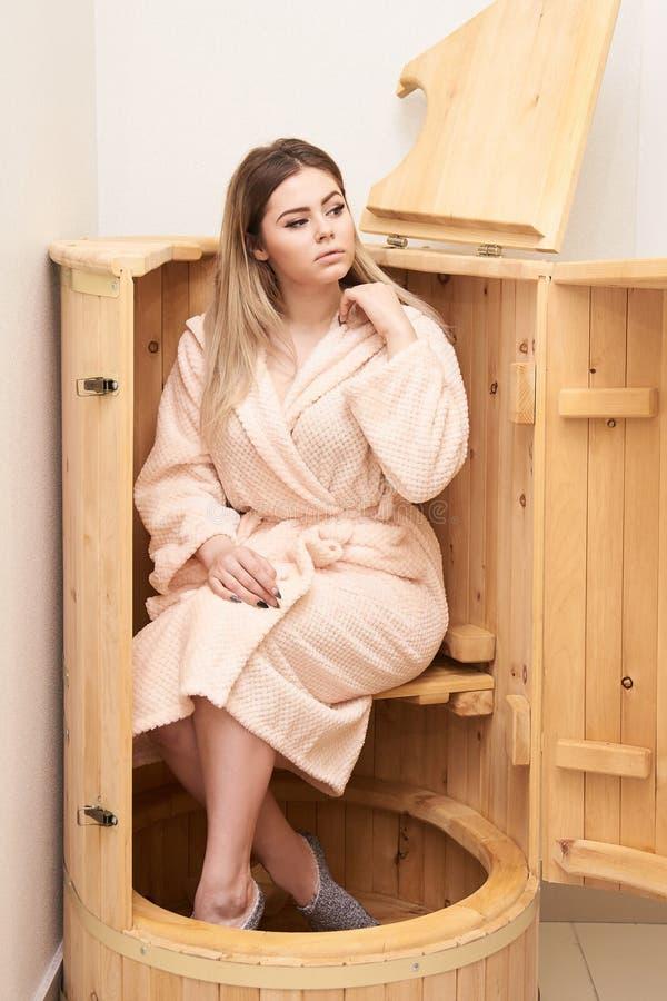 Barrel cedar. Wellness spa sauna. Aromatherapy treatment. Young beauty woman. Girl face stock images