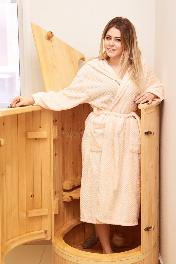 Barrel cedar. Wellness spa sauna. Aromatherapy treatment. Young beauty woman. Girl face stock photo