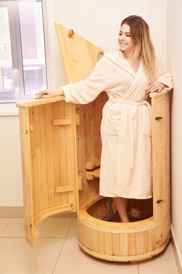 Barrel cedar. Wellness spa sauna. Aromatherapy treatment. Young beauty woman. Girl face royalty free stock photography