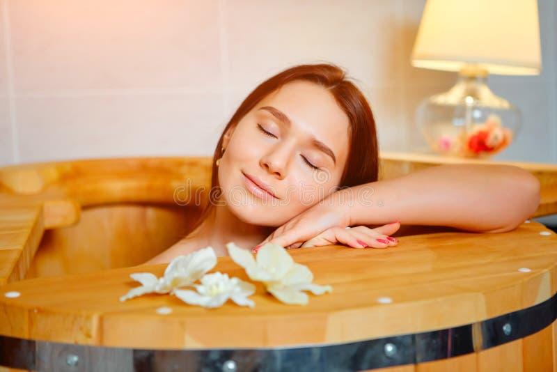Barrel cedar. Wellness spa sauna. Aromatherapy treatment. Young beauty woman. Girl face royalty free stock photos