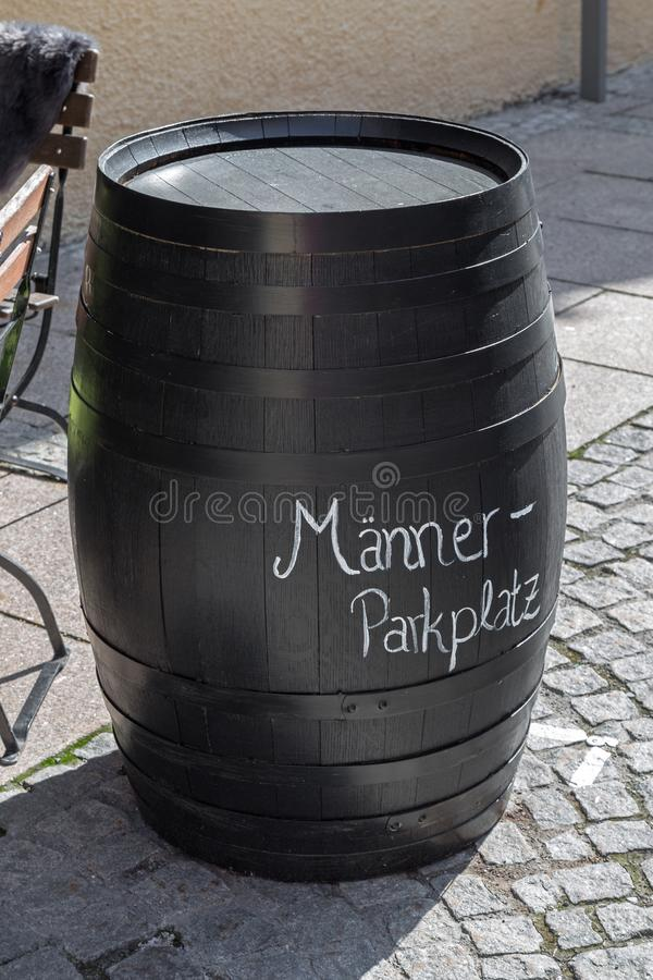"""Barrel with german inscription """"parking lot for men"""". In front of a pub in Bavaria stock images"""