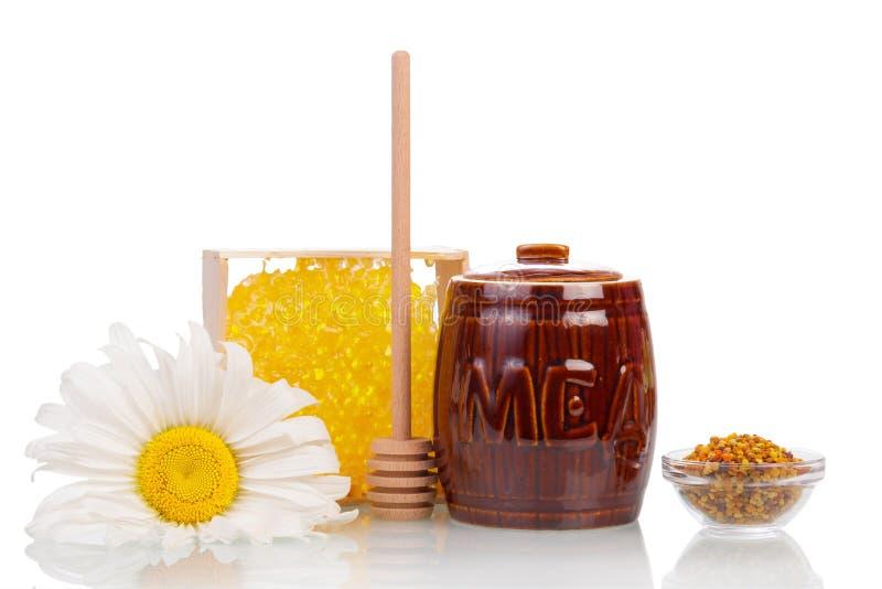 Barrel le miel, le nid d'abeilles, la cuvette de pollen, la poche en bois et la camomille d'isolement photographie stock libre de droits