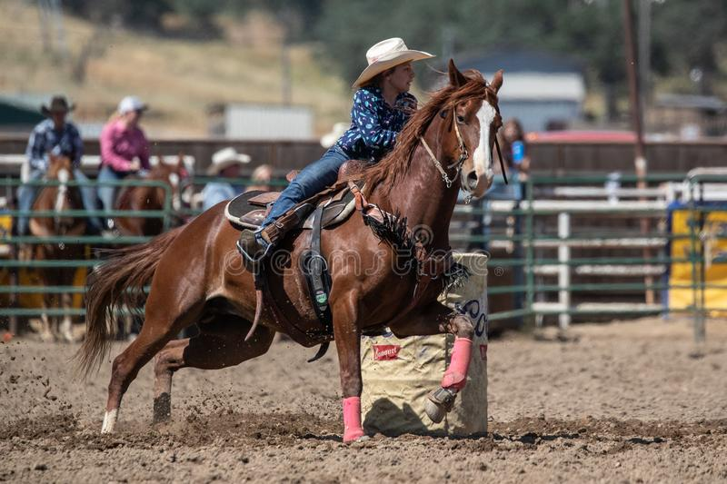 Barrel Racer. Cowgirl barrel racing the clock at the Cottonwood Rodeo in Northern California stock photo