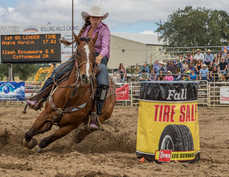Barrel Racer. A cowgirl clears a barrel during a barrel racing event. The rodeo in Cottonwood, California is a popular event on Mother's Day weekend in this royalty free stock photo