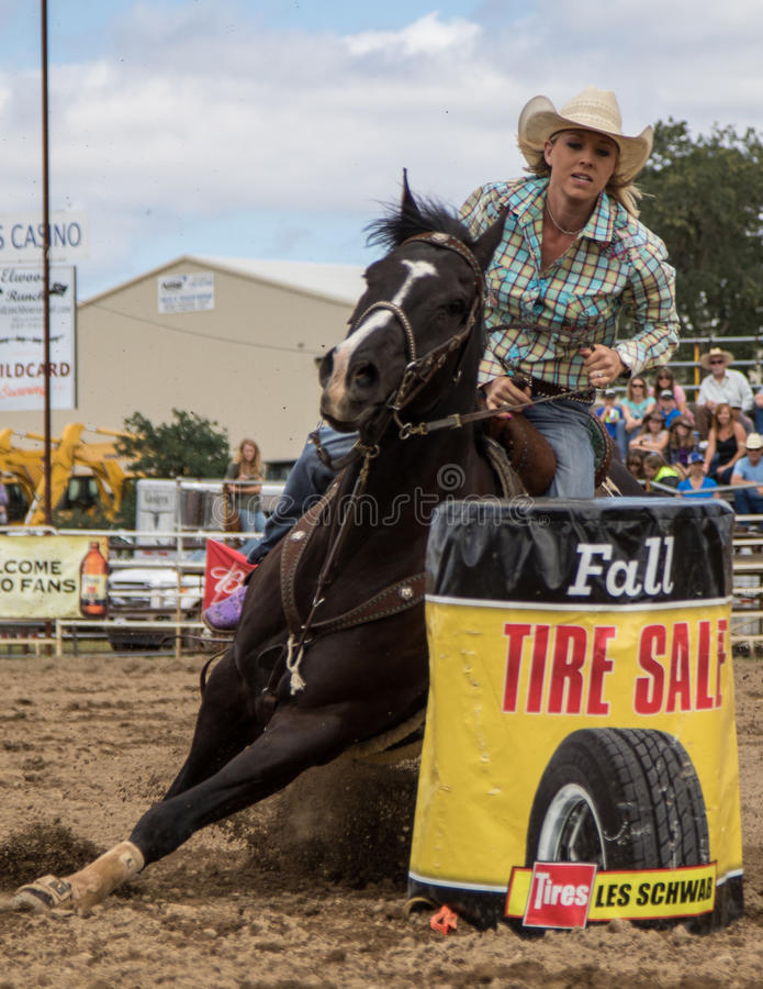 Barrel Racer. A cowgirl clears a barrel during a barrel racing event. The rodeo in Cottonwood, California is a popular event on Mother's Day weekend in this stock images