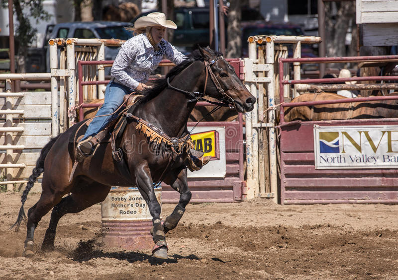 Barrel Racing Rider. A cowgirl rides around a barrel during a barrel racing event. The rodeo in Cottonwood, California is a popular event on Mother's Day weekend stock image