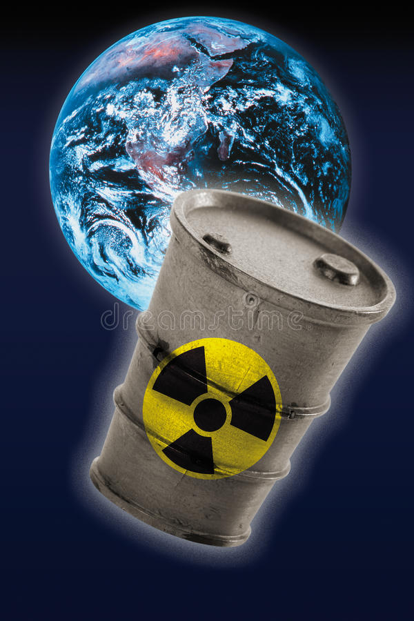 Barrel with signs of radioactivity in front of earth royalty free stock photos