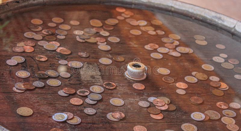 Wooden wishing well with coins royalty free stock photo