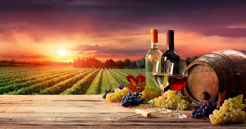 Barrel Wineglasses And Bottle In Vineyard. At Sunset stock images