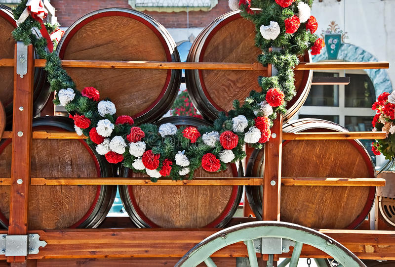 Barrels or Kegs of Beer in Cart. This is many barrels or kegs of beer in a cart, draped with a garland of flowers for a celebration. Horizontal still life with stock photos