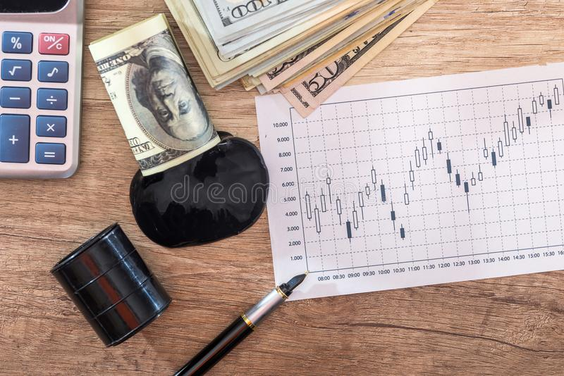 Barrels of oil with dollar banknotes, calculator, profit, business growth graph. On desk stock photos