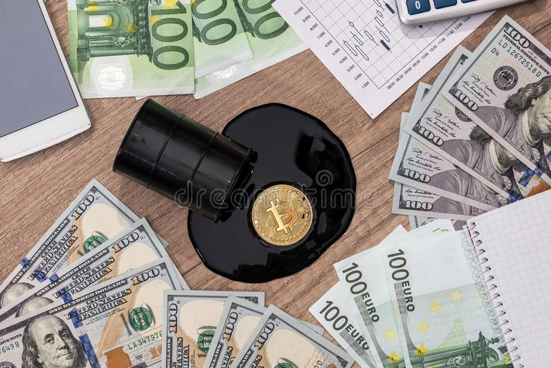 Barrels of oil, dollar, euro, bitcoin, diagram. Pen and calculator stock images