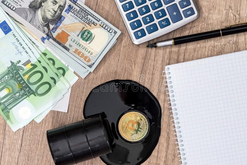 Barrels of oil, dollar, euro, bitcoin, diagram, pen. And calculator stock photography