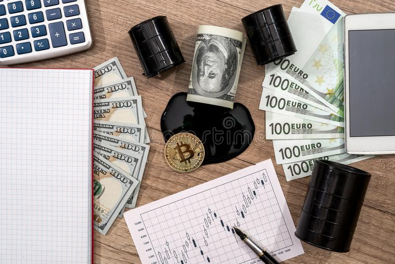 Barrels of oil, dollar, euro, bitcoin, diagram, pen. And calculator stock photo