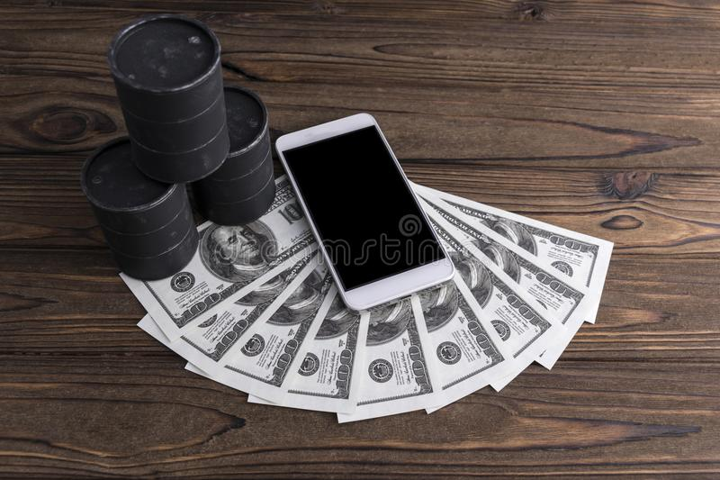 Barrels of oil, dollars, a smartphone with a black screen. On a wooden background. sale rate royalty free stock photo