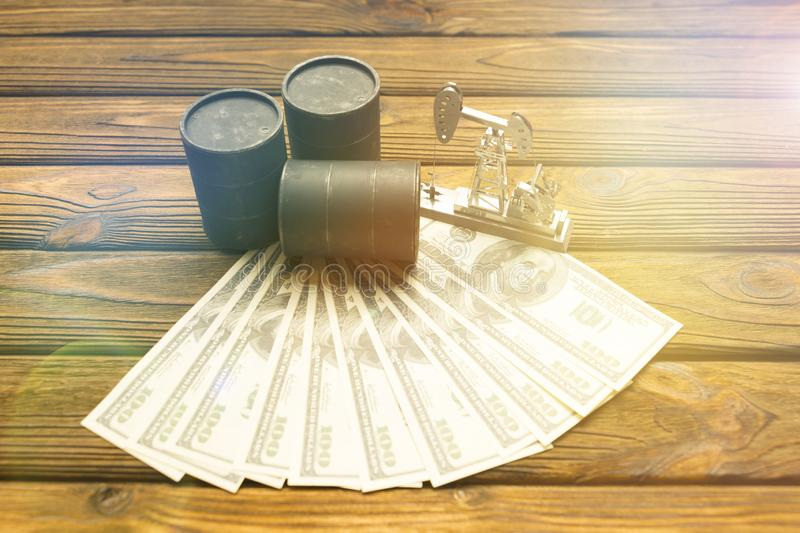 Barrels of oil, neftechka, bills of American dollars. On a wooden background. purchase, sale of oil royalty free stock image