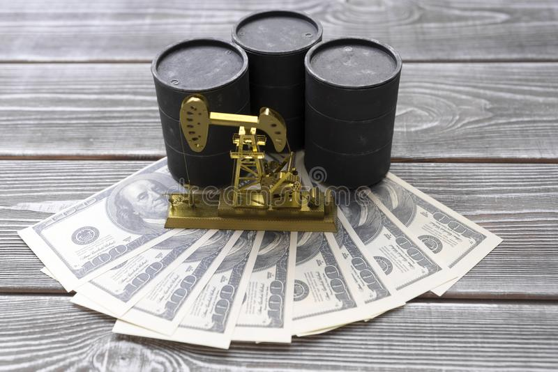Barrels of oil, neftechka, bills of American dollars. On a wooden background. fuel industry stock photography
