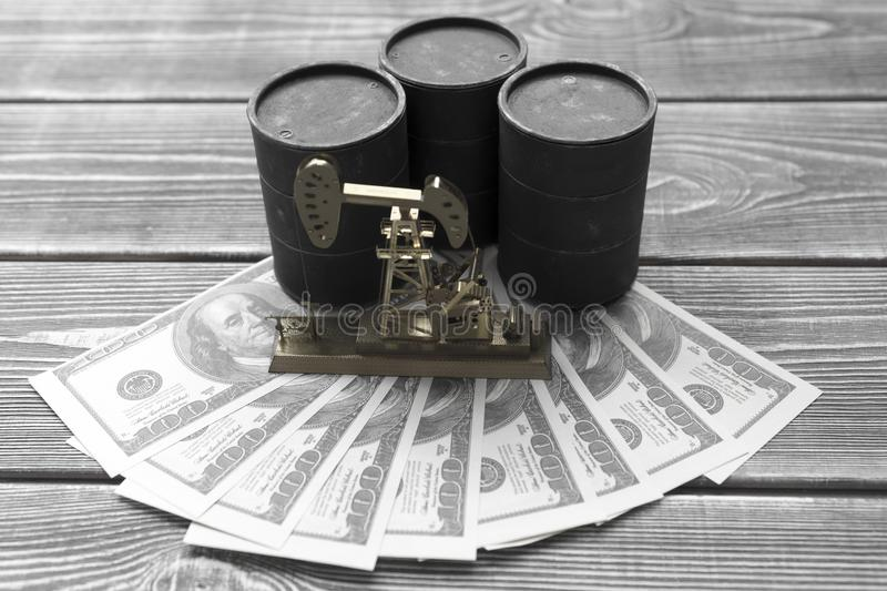 Barrels of oil, neftechka, dollar bills on the background of a wooden table. Purchase, sale of oil royalty free stock image