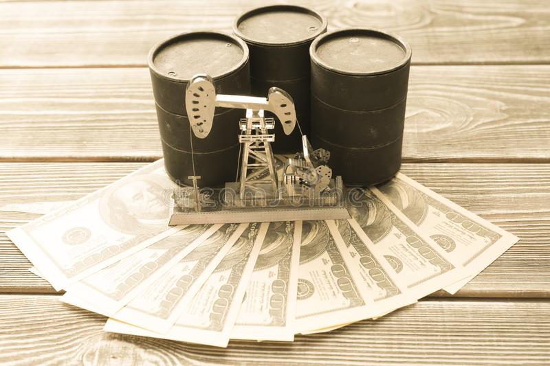 Barrels with oil, neftechka, dollars on a wooden background. Buying, selling, mining of fuel royalty free stock photo