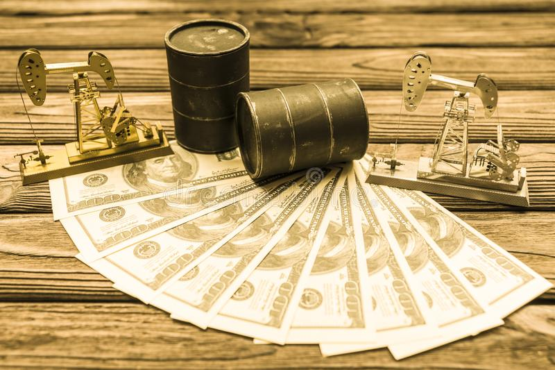 Barrels of oil, US dollars, neftechka on a wooden background. ,. Sale of oil. oil production. fuel industry stock image