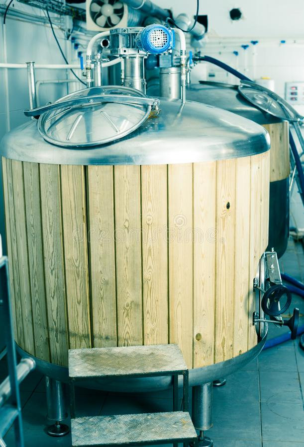 Barrels with wood trimmed for beer fermentation lined in production hall. Steel barrels with wood trimmed for beer fermentation lined in production hall stock photos