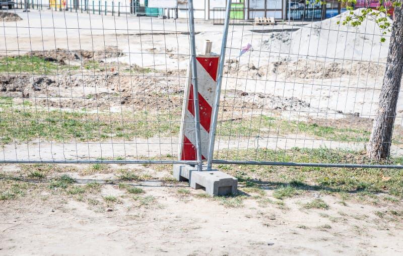 Barrera del emplazamiento de la obra de la obra vial a continuaci?n con la cerca protectora del metal en la reparaci?n urbana de  fotografía de archivo