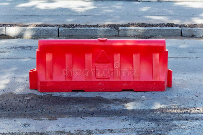 Barrera plástica roja en el camino bajo reparación cerca en el tiempo de trabajo en calle de la ciudad fotos de archivo