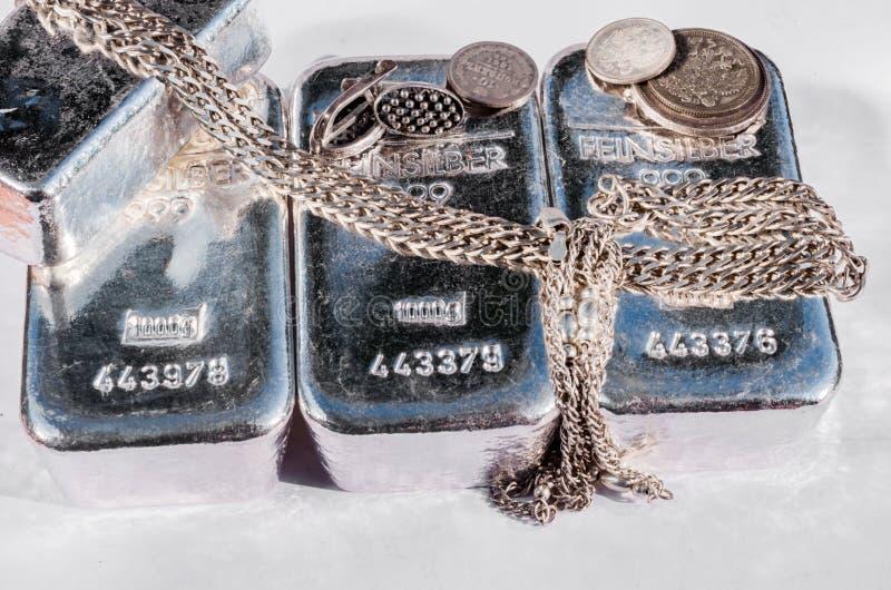 Barres argentées, pièces de monnaie et bijoux de kilogramme sur le fond clair images stock
