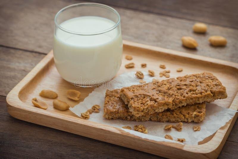 Barres de granola et verre de lait de plat en bois photographie stock