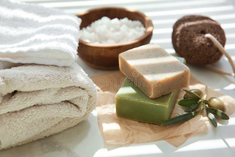 Barres de savon naturel avec l'extrait et les serviettes olives sur la table photo stock