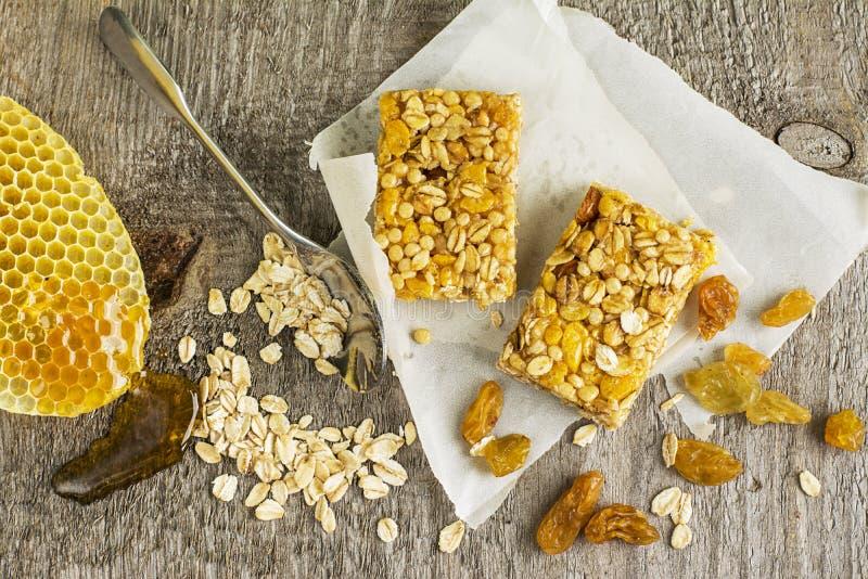 Barres organiques de céréale d'avoine avec du miel et les raisins secs d'or sur un fond en bois simple Vue supérieure photographie stock libre de droits
