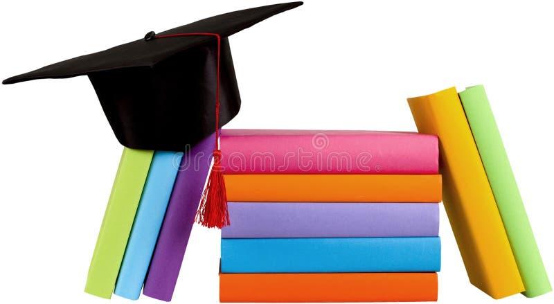 Barrete da graduação sobre a pilha de livros sobre fotografia de stock