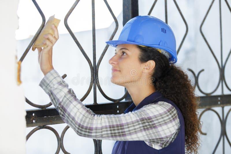 Barriär för metall för kvinnlig byggmästarearbetare polerande royaltyfria foton