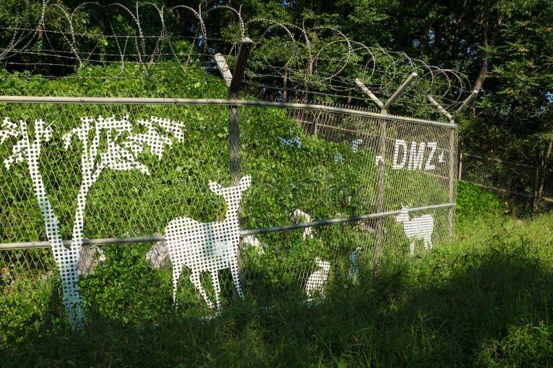 Barrière avec le barbelé dans la nature, les arbres et les buissons verts avec les cerfs communs peints sur la barrière le long d photographie stock libre de droits
