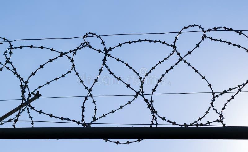 Barrière de barbelé de l'objet protégé contre le ciel photographie stock libre de droits