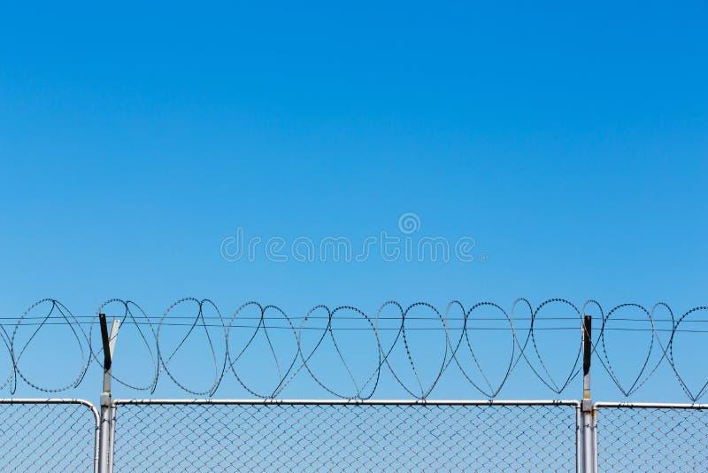 Barrière de barbelé sur le ciel bleu images libres de droits